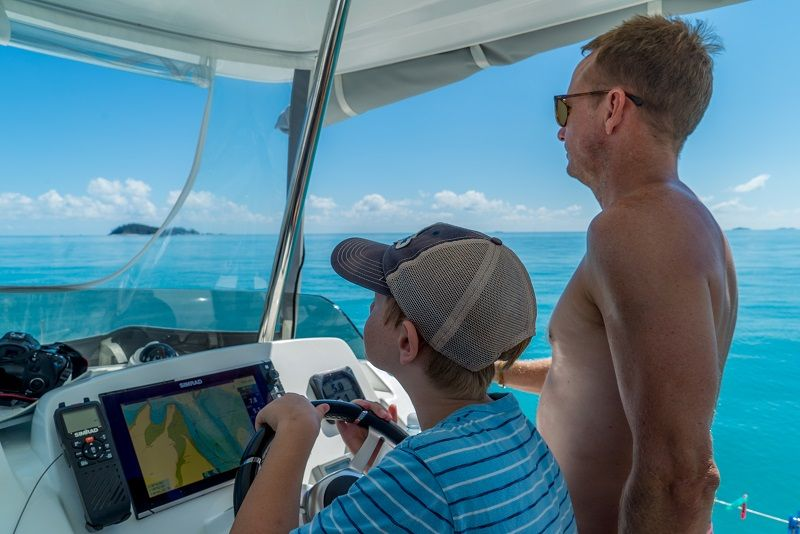 Boy and father navigating a bareboat